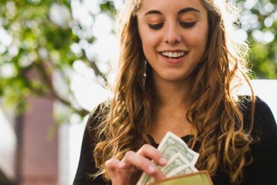 Une fille qui sort de l'argent de son portefeuille